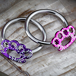 Steel brass knuckles with glitter captive